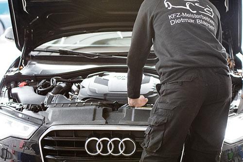 Kfz Meister steht vor einem Audi A4 in schwarz